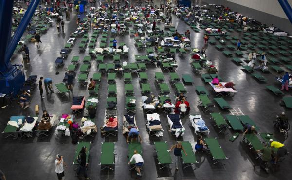 Evacuees fill up cots Monday at the George Brown Convention Center in Houston, which has been turned into a shelter run by the American Red Cross to house victims of the high water from Hurricane Harvey. Experts say it's best to donate money, not items or