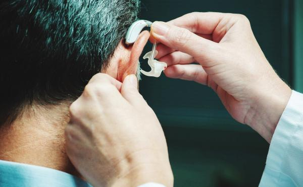 A man gets his hearing aid adjusted. Two large studies show that age-related memory loss can be slowed when older people promptly address hearing and vision loss.