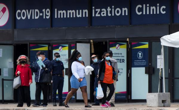 Canada's National Advisory Committee on Immunization is recommending allowing people to mix COVID-19 vaccine doses. Here, people walk past a vaccination clinic this week in Toronto.