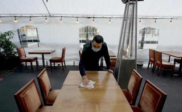 A person cleans a table in an outdoor tented dining area of a restaurant in Sacramento, Calif., on Nov. 19. Job growth slowed sharply in November as relief aid is due to expire at the end of the year.