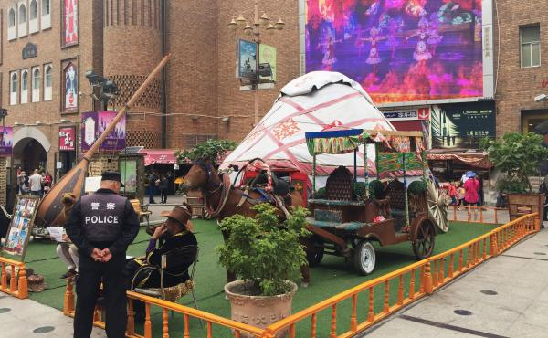 At Urumqi's Grand Bazaar, a police officer chats with a local vendor while a video promoting China's ethnic minorities plays on a big screen overlooking the square. This was the site of Uighur protests in 2009 that sparked citywide riots, leading to the d
