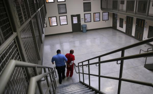 "A guard escorts a detained immigrant from his ""segregation cell"" back into the general population at the Adelanto Detention Facility in November 2013. Today the privately run ICE facility in Adelanto, Calif., houses nearly 2,000 men and women and has come"