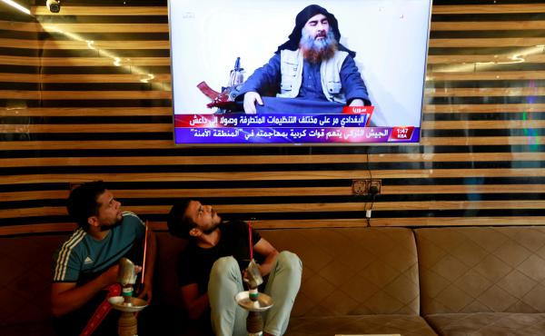 Iraqi youth watch the news about ISIS leader Abu Bakr al-Baghdadi's death, in Najaf, Iraq, on Sunday.