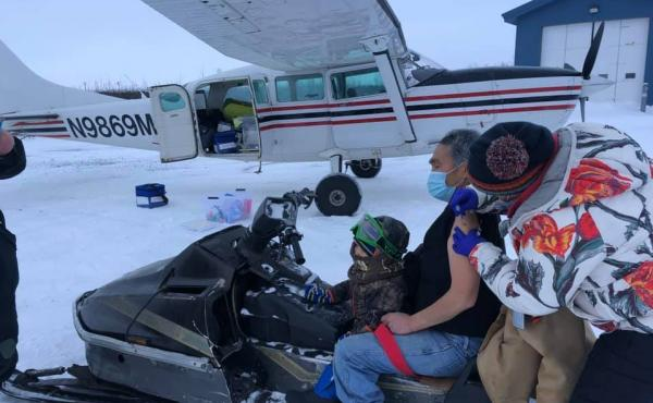 Sarah Lind, a nurse with Yukon-Kuskokwim Health Corp., Southwest Alaska's tribal health care provider, vaccinates James Evan in December. They're standing on the tarmac in the village of Napakiak, where Evan works for YKHC at the clinic.