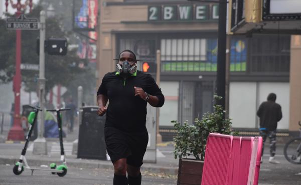 A Portland, Ore., resident wears a respirator to protect himself from wildfire smoke as he jogs in downtown in September 2020.