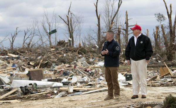 President Donald Trump speaks with a Putnam County rescue worker as he tours the damage left by the tornadoes in Cookeville, Tenn.