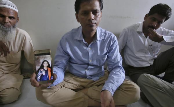 Abdul Aziz Sheikh (center), the father of Sabika Sheikh, a victim of a shooting at a Texas high school, shows a picture of his daughter in Karachi on Saturday.