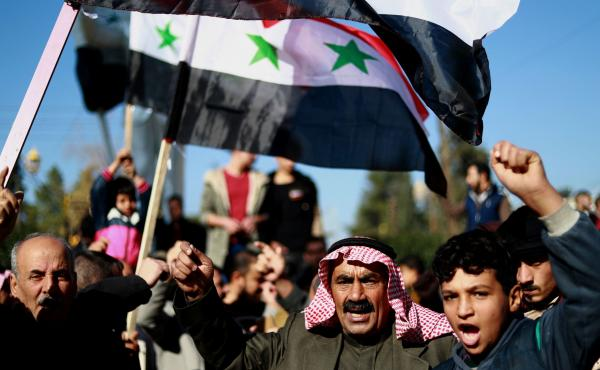 Syrian demonstrators wave the national flag during a demonstration in the Kurdish-majority city of Qamishli in northeastern Syria on Sunday, asking for the Syrian army's protection as Turkey threatens to carry out a fresh offensive following the U.S. deci