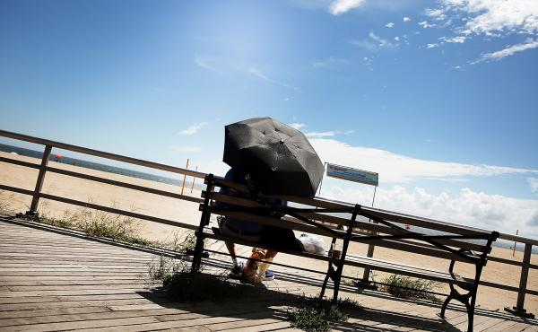 A man finds a bit of shade on the boardwalk at Brighton Beach in New York City.