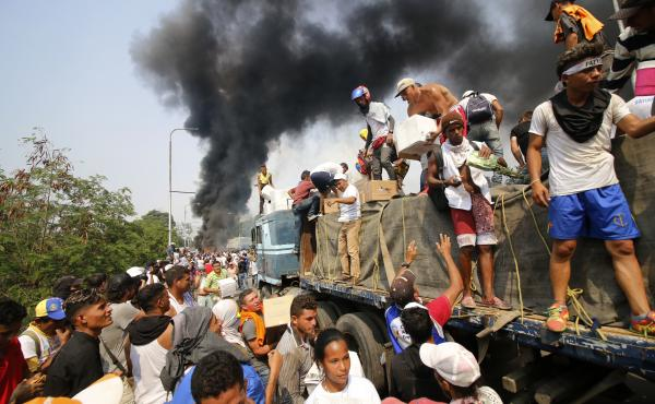 People try to salvage humanitarian aid after the truck carrying it was set ablaze on the Francisco de Paula Santander International Bridge between Colombia and Venezuela, on Feb. 23.