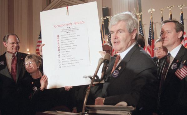 """Then-House Speaker Newt Gingrich holds up a score card during a Republican rally at Capitol Hill in February of 1995. The rally was to mark progress the GOP made on their """"Contract with America"""" in the early days of the """"Republican Revolution."""""""