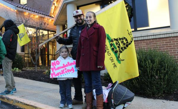"""Outside City Hall on the evening of a vote on a proposed mask order in Washington, Mo., residents Ali and Duncan Whittington protest against the order, along with their 4-year-old daughter. """"I'm here because I feel my freedom is being violated,"""" Ali says."""