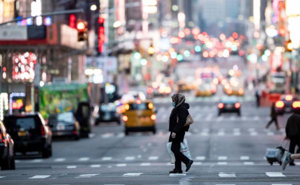 A woman wearing a mask crosses the street in Times Square in Manhattan on March 17. The coronavirus outbreak has exposed racial divisions in the U.S. — as well as geographic ones.