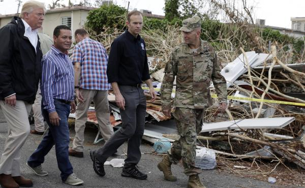 President Donald Trump walks with FEMA administrator Brock Long, second from right, and Lt. Gen. Jeff Buchanan, right as he tours an area affected by Hurricane Maria in Guaynabo, Puerto Rico, on Oct. 3, 2017.