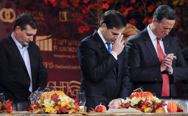 Republican U.S. presidential candidates Ted Cruz, Marco Rubio and Rick Santorum pray at the Presidential Family Forum in Des Moines, Iowa, November 20, 2015. The question of how to treat Syrian refugees has evoked different reactions in political evangeli