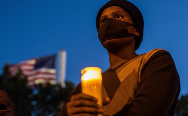 A man holds a candle during a vigil around a makeshift memorial at the tree where Robert Fuller was found dead hanging from a rope in Palmdale, Calif. Officials deemed Fuller's death a suicide, but his family wants an independent investigation.