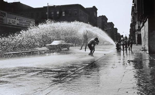 """""""Hydrant: In the Air,"""" 1963 — """"It's significant because it shows us. We were not allowed to go to the public pools. So we opened our hydrant and we cooled ourselves off. But when I saw it and photographed it I made it more than just poor people turning"""