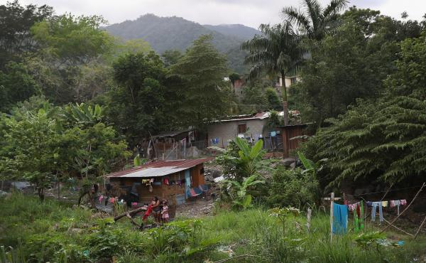 Families live by a creek in an impoverished neighborhood in San Pedro Sula, Honduras.