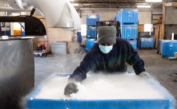 An employee makes dry ice pellets at Capitol Carbonic, a dry ice factory in Baltimore in Nov. 2020. Dry ice helps keep COVID-19 vaccines cool during transport.