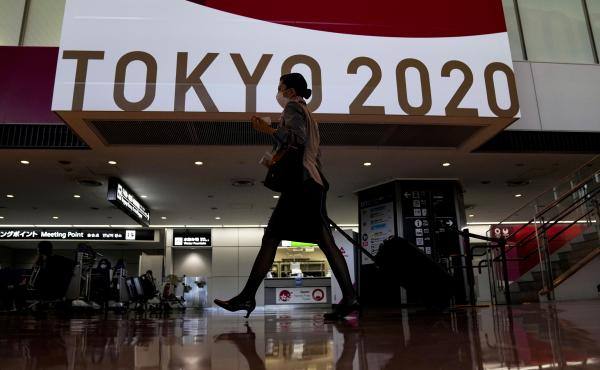 A flight attendant walks by a large display of Tokyo 2020 Olympics at Narita International Airport on Thursday in Narita, east of Tokyo.