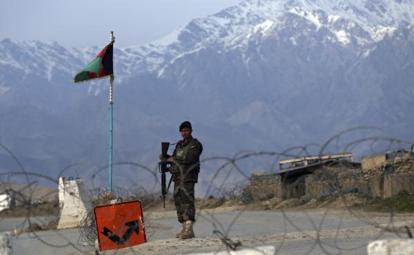 An Afghan National Army soldier stands guard at a checkpoint near the Bagram airfield, the largest U.S. military base in Afghanistan, in April.