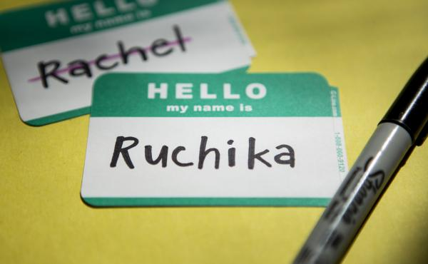 """A name tag that reads """"Hello my name is Ruchika"""" sits on a yellow background with a permanent marker next to it. Behind and to the left of the name tag, is another name tag that reads """"Hello my name is Rachel"""" with """"Rachel"""" crossed out."""