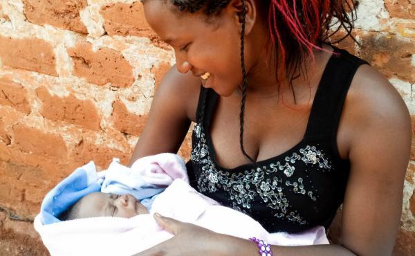 Maria Nalubega holds her three-week-old baby daughter.