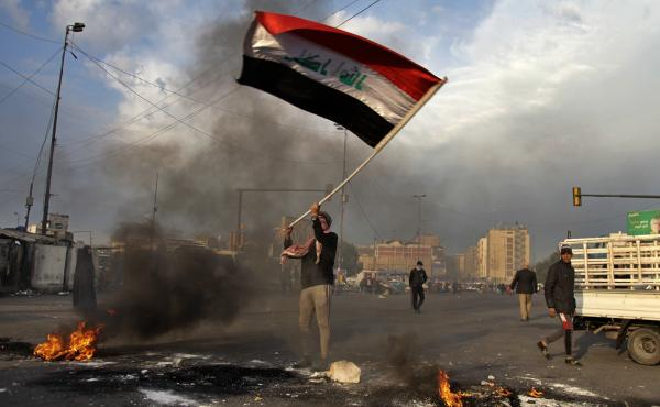 A protester waves the Iraqi flag in Baghdad on Wednesday. Both the U.S. and Iran have launched attacks in Iraq in the past week — including the Iranian missile strike on bases housing U.S. military personnel.