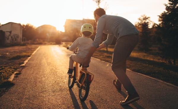 Photo of a young boy and his father on a bicycle lane, learning to ride a bike.