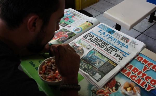 """A Salvadoran man reads a newspaper at a market in San Salvador on January 8. The newspaper headline reads: """"The United States will decide today the future of TPS."""""""