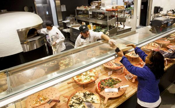 A customer receives a slice of pizza from the prepared food section of the new Whole Foods Market Inc. store in downtown Los Angeles. Prepared foods sold at supermarkets, big-box and convenience stores are a bigger and bigger portion of those companies' p