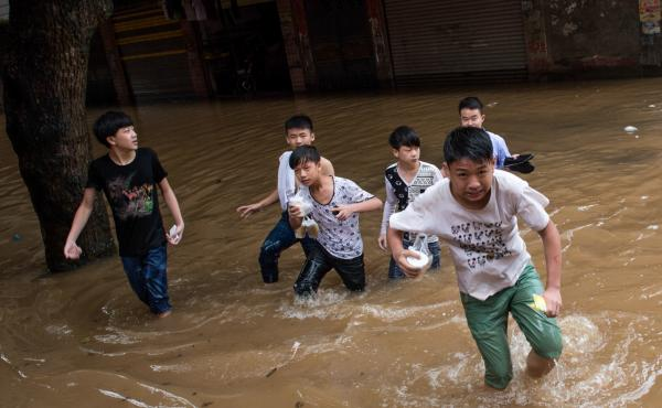 Children wade in a flooded street last June in Leiyang, China.