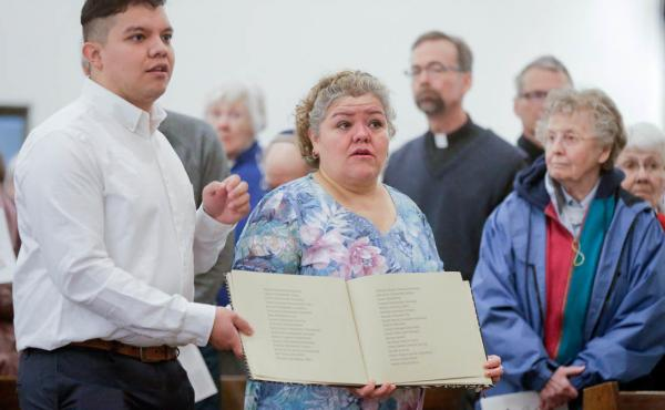 During a service at St. Bridget Catholic Church in Postville, Iowa, last year, Consuelo Lopez (center, right) and her son Pedro carry a book containing the names of those arrested and detained during a 2008 Immigration and Customs Enforcement raid on a lo