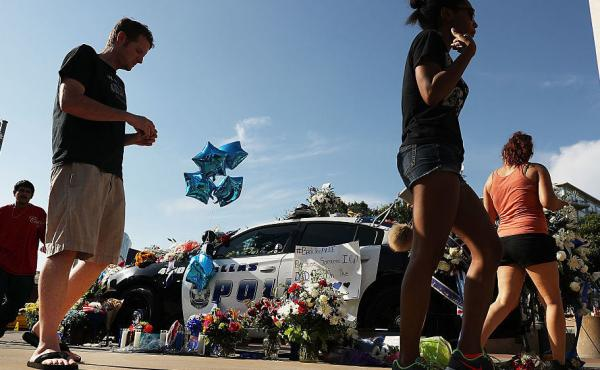 People write condolence notes and lay flowers at a growing memorial in front of the Dallas Police Headquarters near the area that is still an active crime scene in downtown Dallas following the deaths of five police officers last night on July 8, 2016 in