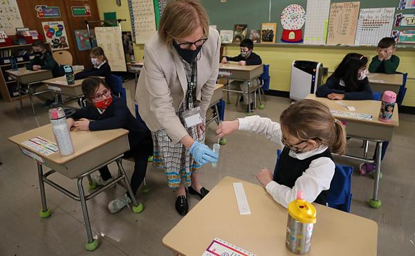 A student gives her coronavirus swab to Helenann Civian, the principal of South Boston Catholic Academy in Boston in January. The White House announced $10 billion to expand testing in K-12 schools.