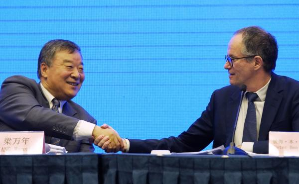 "Peter Ben Embarek, of the World Health Organization team (right) shakes hands with Liang Wannian, his Chinese counterpart, after a news conference on Tuesday in Wuhan, China. The White House says it has ""deep concerns"" over how initial findings were commu"