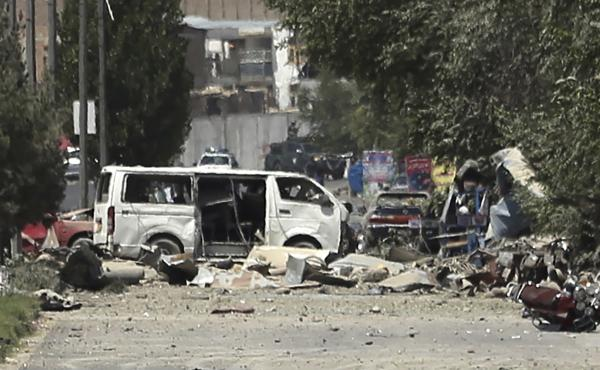 A destroyed white van sits at the site of an explosion in Kabul, Afghanistan, Monday. A powerful bomb blast tore through the capital, rattling windows, sending smoke billowing from Kabul's downtown area and wounding more than a hundred people.