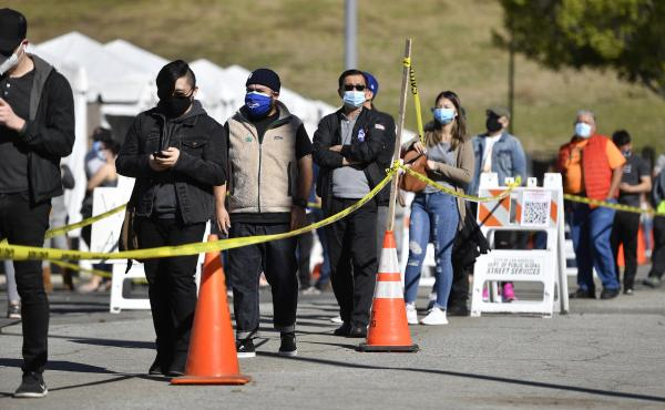 The U.S. wants at-home coronavirus testing to be widely available, to help Americans return to normal life. Here, people wait in a long line at a coronavirus testing and vaccination site at Lincoln Park in Los Angeles.