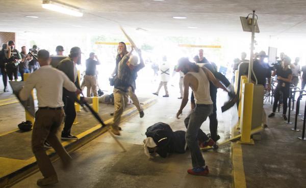 DeAndre Harris, on the ground, is assaulted in a parking garage beside the Charlottesville, Va., police station on Aug. 12, 2017, after a white nationalist rally was dispersed by police.