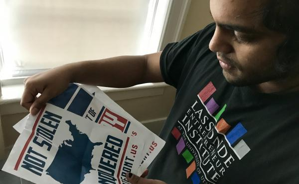 Mohan Sudabattula, a senior at the University of Utah, shows posters he found on campus from the white nationalist group Patriot Front.