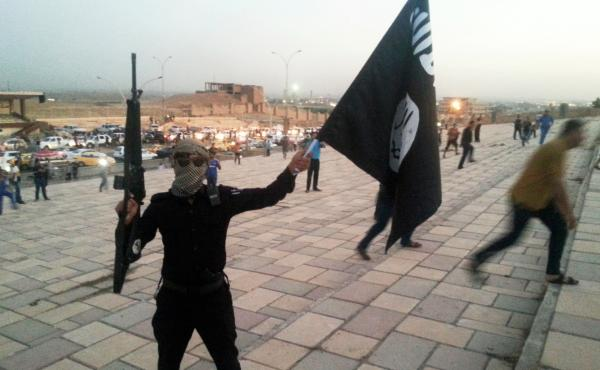 An Islamic State fighter holds holds a rifle and the group's flag shortly after capturing the northern Iraqi city of Mosul in June 2014. Dozens of Americans have been accused of planning or heading off to the Middle East to join the group. Their individua