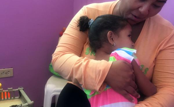 Susette, age 4, with her mother, Carmen. The child's father left Venezuela for Chile to earn money to send back home.