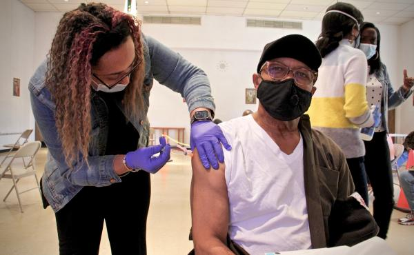 Thomas W. Munson receives his second dose of COVID-19 vaccination from registered nurse Elizabeth Lash at a Sayre Health clinic held at Tablenacle Lutheran Church in West Philadelphia.