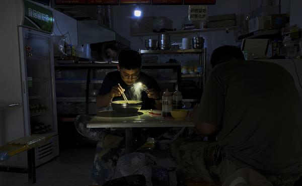 A man uses his smartphone flashlight to light up his bowl of noodles as he eats breakfast at a restaurant during a blackout in Shenyang, in northeastern China's Liaoning province, Wednesday. People ate breakfast by flashlight and shopkeepers used portable