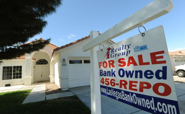 A house under foreclosure in Las Vegas displays a sign on Oct. 15, 2010, saying that it's now bank-owned. Sen. Sherrod Brown has vowed increased scrutiny of Wall Street banks, in part after a surge in foreclosures in his hometown in Ohio over a decade ago