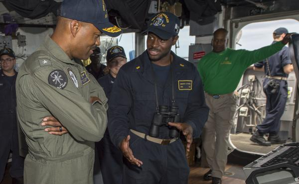 Rear Adm. Alvin Holsey (left) speaks with Ensign Dimitri Foster in the pilothouse aboard guided-missile cruiser USS Lake Champlain in 2018.