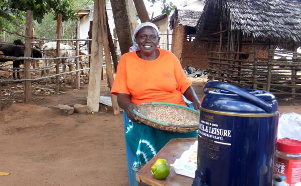 Bertha Ngumbi, mother of five children who are all now grown, at her farm in Kenya. She's sifting through beans to get rid of bad ones and stones. The cows' and goats' houses are behind her.