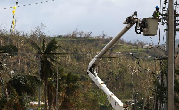A worker repairs power lines in San Isidro, Puerto Rico. An outdated, aboveground power grid coupled with a comparative shortage of utility workers have hobbled efforts to restore power in the territory.