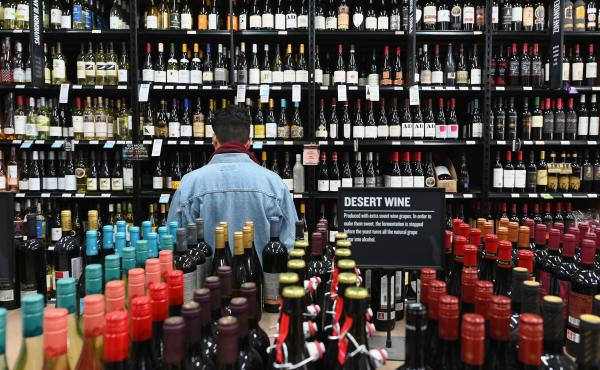 A patron stands in front of a shelf of wine bottles at The Liquor Store.Com in Brooklyn, N.Y., last March.