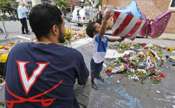 Pastor Daniel Xisto and his son Max, 2, look over a makeshift memorial on Monday for Heather Heyer, who was killed in a car attack on Saturday after a white nationalist rally in Charlottesville, Va. While many are calling the attack an act of domestic ter